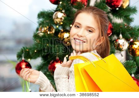 bright picture of happy woman with shopping bags and christmas tree.....