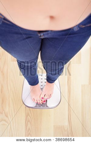 Woman on a bathroom scale hiding the numbers - diet and overweight concept