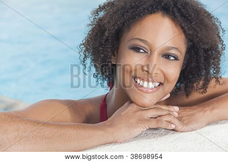 A beautiful sexy young African American girl or young woman wearing a bikini and relaxing on the side of a swimming pool.