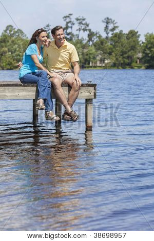 Portrait shot of an attractive, successful and happy middle aged man and woman couple in their thirties, sitting together on a jetty or pier by a lake
