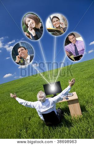 Business or social network connections concept photograph of man businessman sitting at a desk using a computer in a green field raising her arms into a bright blue sky
