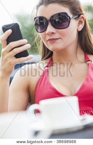 A beautiful young woman texting on her mobile cell phone while drinking coffee in a cafe