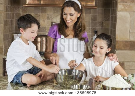 An attractive smiling family of mother and two children, girl boy, son daughter, baking in a kitchen at home