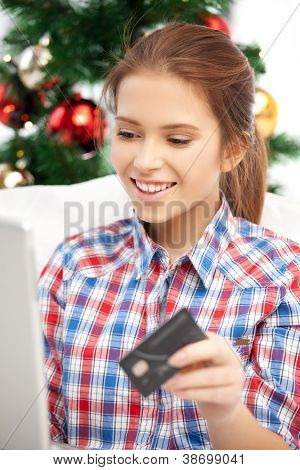 happy woman with laptop computer and credit card over christmas tree....
