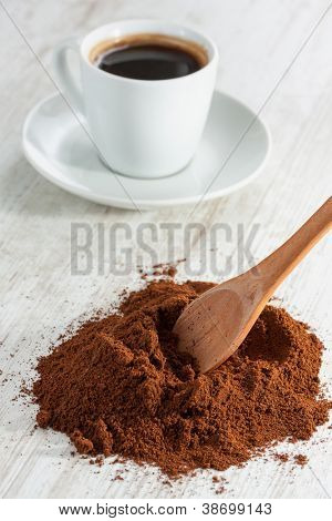 Wooden spoon with freshly ground coffee and a cup