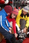 foto of ski boots  - Family Trying On Ski Boots In Hire Shop - JPG