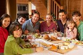 stock photo of chalet  - Two Familes Enjoying Meal In Alpine Chalet Together - JPG