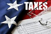 stock photo of irs  - Portrayal of tax time with government 1040 tax form reading glasses flag and the word  - JPG