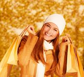 Image of attractive cheerful woman with brown shopping bags on golden autumn background, closeup por