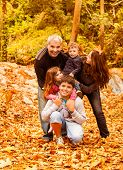 Photo of five happy person have fun outdoors, beautiful young parents play with two little children