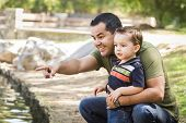 image of three life  - Happy Hispanic Father Points with Mixed Race Son at the Park Pond - JPG