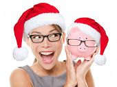Christmas glasses eyewear sale concept. Woman wearing eye glasses and santa hat is holding piggy ban