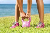 Fitness - kettlebell woman cross training outside on crass lifting kettlebells. Closeup of