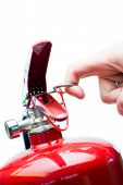 stock photo of pressure vessel  - Hand pulling safety pin from red fire extinguisher - JPG