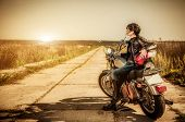 stock photo of biker  - Biker girl sits on a motorcycle - JPG