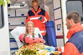 stock photo of accident victim  - Woman with broken arm in ambulance paramedics accident helping victim - JPG