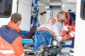 stock photo of oxygen  - Paramedics putting patient man oxygen mask in ambulance car - JPG