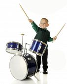An adorable preschooler behind a drum set.  He's pretending to conduct an orchestra with his drum st