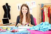 stock photo of dress mannequin  - beautiful young dressmaker in workroom - JPG