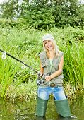 stock photo of fisherwomen  - woman fishing in pond - JPG