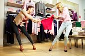 stock photo of greedy  - Image of two greedy girls fighting for red tanktop in department store - JPG