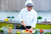 Image of male chef with knife cutting vegs on wooden board poster