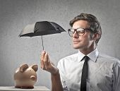 Businessman protecting a piggy with a little black umbrella