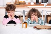 stock photo of pouting  - Kids pouting in the kitchen - JPG