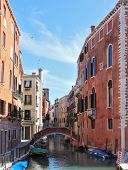 Eternal fabulous Venice. Through a narrow channel constructed an elegant bridge. Gondola approached