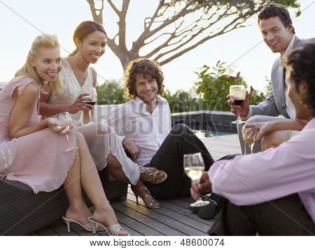 Group of multiethnic friends drinking and socialising on porch