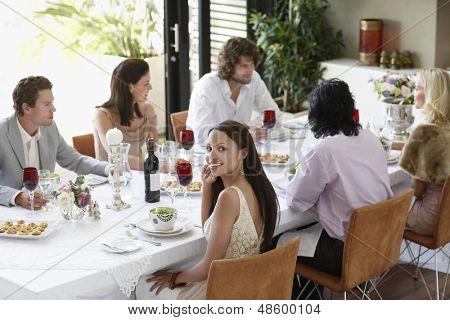Retrato de mujer joven hermosa con amigos teniendo una cena en casa