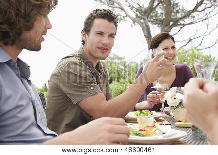 Joven guapo con amigos disfrutando la cena al aire libre