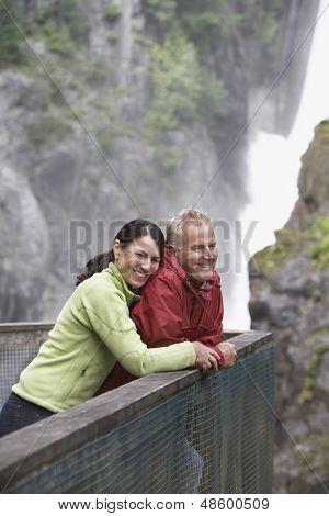 Vista lateral de un medio feliz entre hombre y mujer mirando la vista contra la cascada