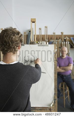 Rear view of a male artist drawing charcoal portrait of model in studio