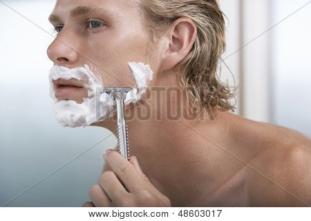 Closeup of handsome young man shaving in bathroom