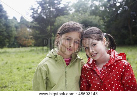 Closeup portrait of two smiling young girls in raincoats on meadow