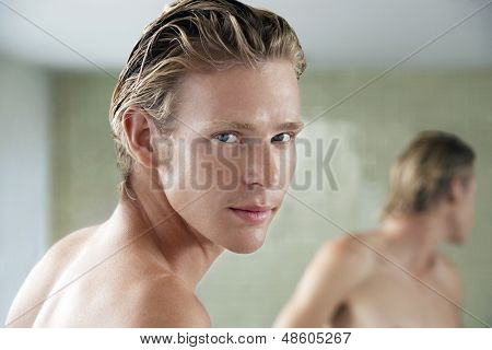 Closeup portrait of handsome young man standing in front of bathroom mirror