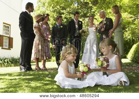 Cute little bridesmaids holding bouquets with guests in background