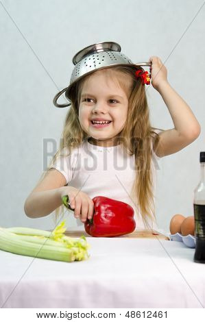 Girl playing in the cook put on a colander on his head