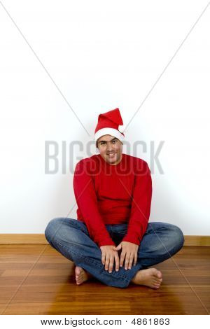 Young Man With Santa Claus Hat Sitting In The Floor