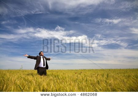 Businessman With His Arms Wide Open In Rural Field