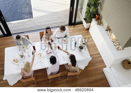 High angle view of multiethnic friends toasting wine across table at dinner party