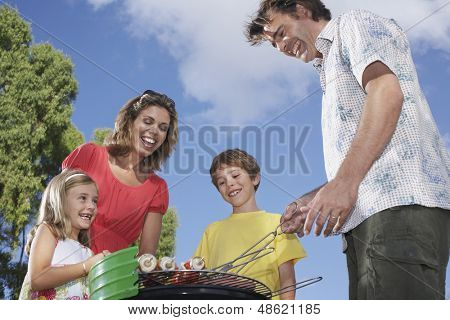 Low angle view of a cheerful couple with two children around the grill in garden