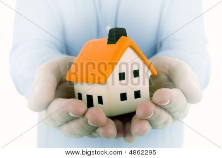 Hombre que sostiene una pequeña casa en sus manos con efecto de sueño para acentuar la casa
