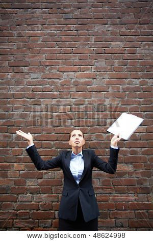 Image of perplexed businesswoman with open palms on background of brick wall