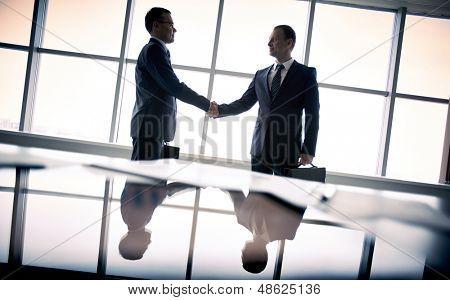 Siluetas de dos empresarios de pie por la ventana y el apretón de manos