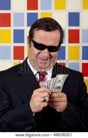 Middle aged repulsive businessman is counting and showing off his money.