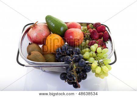 Frutas frescas en un escurridor sobre fondo blanco.