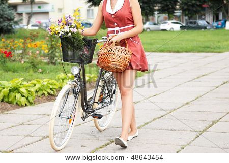 young pretty woman with bicycle and flowers