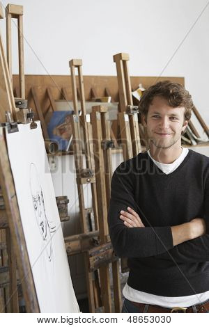 Portrait of a smiling male artist standing by charcoal portrait in studio